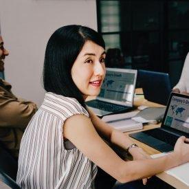 Woman writing at computer desk